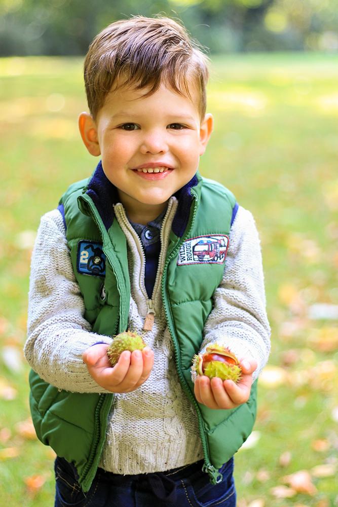 Portrait von Junge im Herbst mit Kastanien in der Hand
