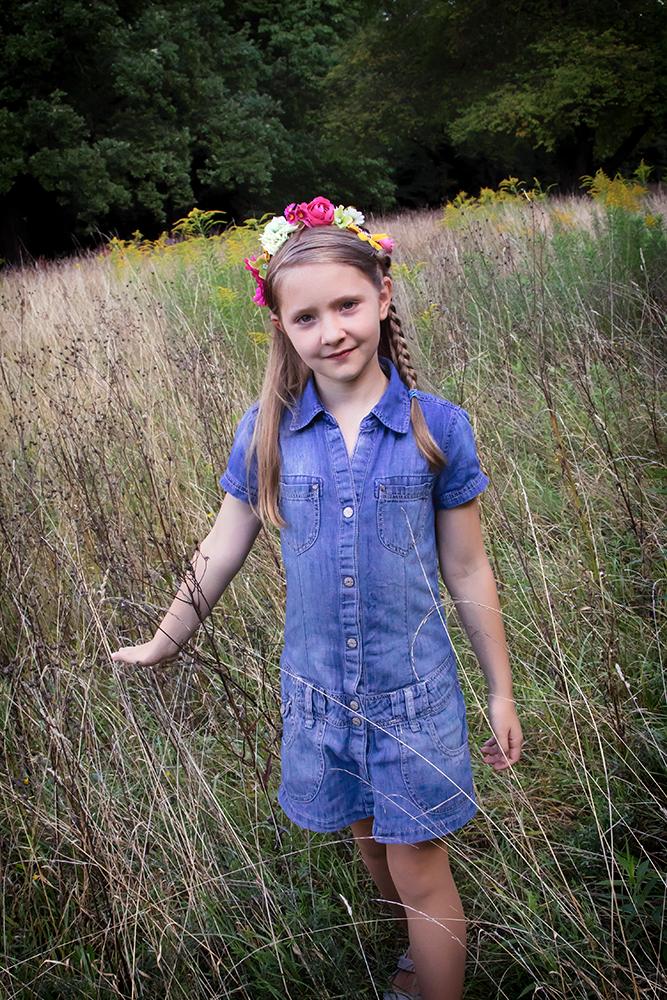 Portrait von Mädchen mit Blumenband im Haar geht über eine hochstehende Wiese