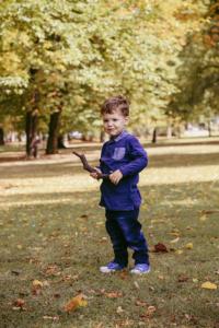Ganzkörperportrait von Junge mit Stock in der Hand auf Herbstwiese
