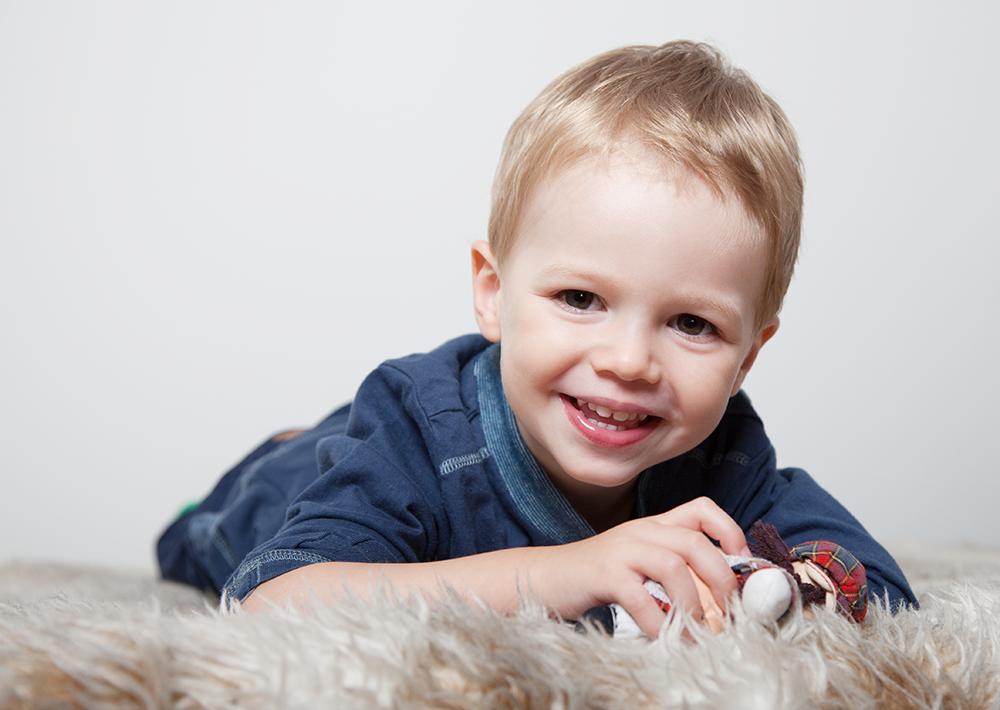 lachender Junge im Portrait auf einer Decke