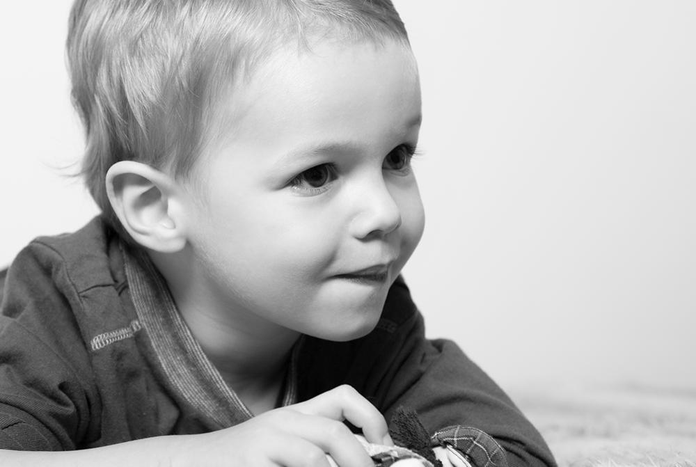 Schwarzweißportrait von kleinem Jungen auf Decke